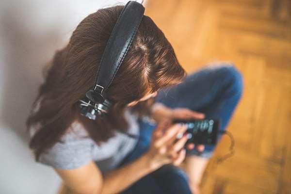 Kvinna som lyssnar på talböcker via sin telefon